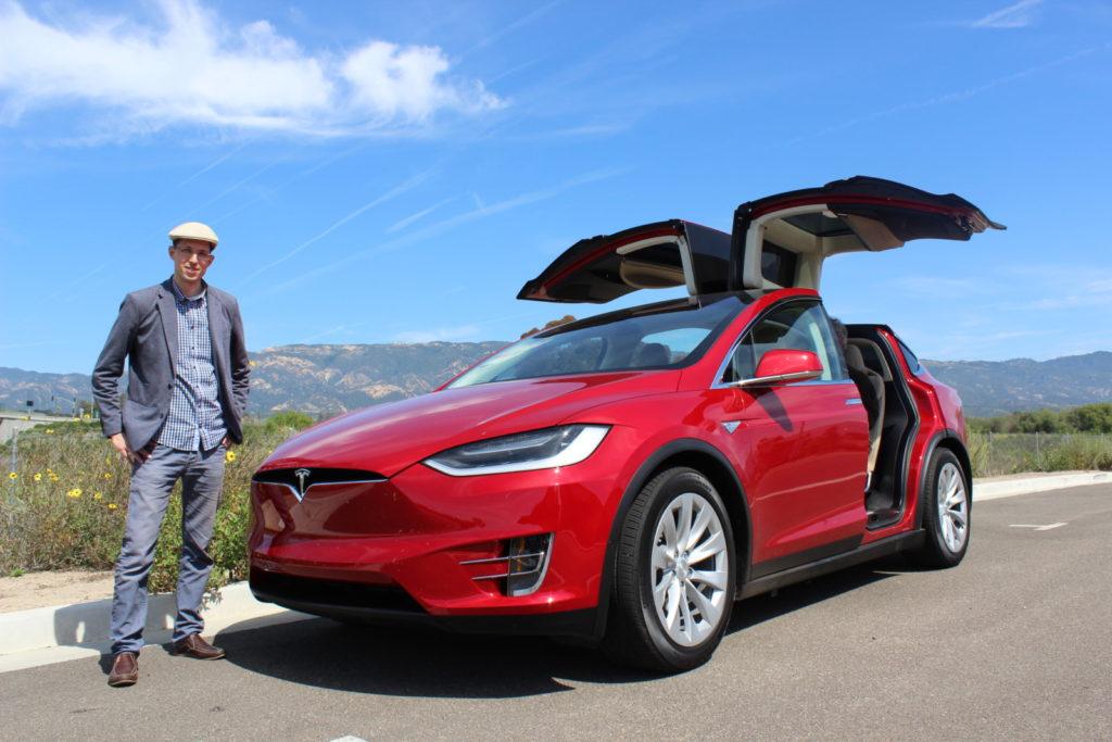 Zachary Shahan beside a Tesla Model X